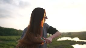 The girl brushes long light brown hair, standing in park at sunset, slow motion. The girl brushes long light brown hair with cute black painted folk brush stock video