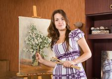 Girl with brushes near  easel Stock Images