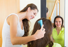 Girl brushing her friend at home Royalty Free Stock Photo