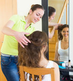 Girl brushing her friend at home Royalty Free Stock Photos