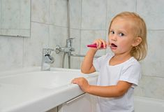 Girl brushing her teeth in the bathroom Stock Photography