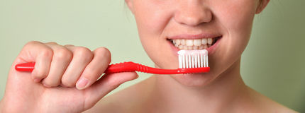 Girl brushing her teeth closeup, dental care concept