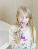 Girl brushing her teeth electric toothbrush with your mouth open. stock images