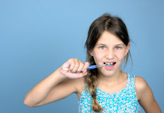 Girl brushing teeth. Against a blue background, leaving room for typing. Photo was taken in september 2014 stock photos