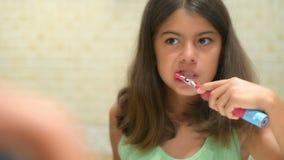 Girl Brushing Teeth. Beautiful mixed race girl brushing teeth looking in the mirror stock video