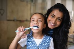 Girl brushing teeth with mother in bathroom Royalty Free Stock Images