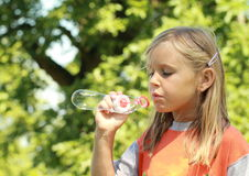 Girl with bubble blower Stock Images