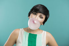 Girl with a bubble gum. Portrait of a beautiful girl with a bubble gum on the mouth, against a blue background Stock Photography