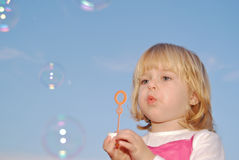 Girl with bubble wand and bubbles Stock Image