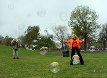 Girl with bubbles. Girl playing with bubbles in a park Royalty Free Stock Image