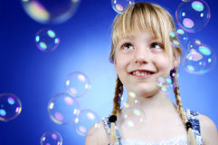 Girl with bubbles. Little girl is looking at some dancing soap bubbles Royalty Free Stock Photos