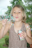Girl and Bubbles. Front view of an eight year old girl blowing bubbles. Child is in focus and bubbles are not. Focus is on the child royalty free stock images
