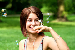 Girl and bubbles. A young woman playing with soap bubbles in a garden stock photo
