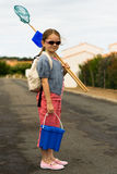 Girl Bucket Beach. A girl pauses as she walks to the beach with a bucket, shovel, and net stock photo
