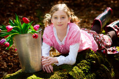 Girl with bucket full of tulips Royalty Free Stock Image