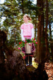 Girl with bucket full of tulips in a forest Royalty Free Stock Photography