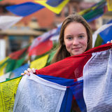 Girl and Buddhist prayer flags flying in the Buddhist monastery. Royalty Free Stock Image
