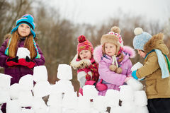 Girl build wall from snow bricks with three children Stock Photo