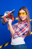 Girl builder in the construction helmet and goggles with a construction tool on a blue background Royalty Free Stock Image