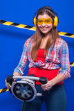 Girl builder in the construction helmet and goggles with a construction tool on a blue background Stock Image