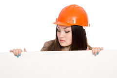 Girl builder in helmet looking at a blank banner. Stock Image