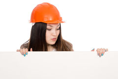 Girl builder in helmet looking at a blank banner Royalty Free Stock Photography