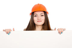 Girl builder in helmet showing a blank banner. Royalty Free Stock Photos