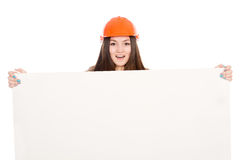 Girl builder in helmet showing a blank banner. Royalty Free Stock Images