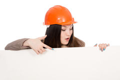 Girl builder in helmet showing a finger on a blank banner. Stock Images