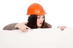 Girl builder in helmet showing a finger on a blank banner. Stock Images