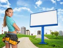 Girl builder in toolbelt. Large billboard, road Stock Photo