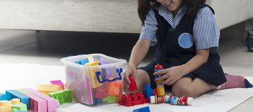 Girl building with colorful toy bricks on the carpet stock photo