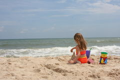 Girl building sand castle 2. A young girl on the beach building a sand castle Stock Photos