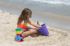 Girl building sand castle 3. A young girl on the beach building a sand castle Royalty Free Stock Images