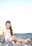 Girl builds. Cute little girl builds a mound of stones on the beach Royalty Free Stock Photo