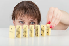 Girl builds line of dominoes counters close up Royalty Free Stock Image