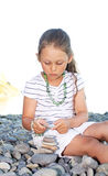 Girl  builds a pyramid. Little girl intently builds a pyramid of sea pebbles Royalty Free Stock Image