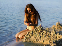 Girl builds a sand castle on the beach Stock Photos