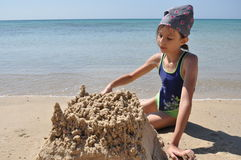 The girl builds a sand castle on the beach. Vacation Stock Photography