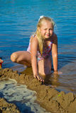 Girl builds a sand castle Stock Photos
