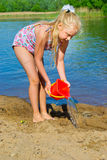 Girl builds a sand castle Stock Photography