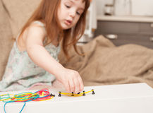 Girl builds shapes from colored rubber bands royalty free stock images