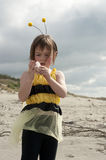 Girl in bumble bee costume playing at beach Royalty Free Stock Images