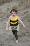 Girl in bumble bee costume playing at beach Stock Photos