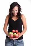 Girl with bunch of apples. Young girl with a bunch of red and green apples in hands Stock Image