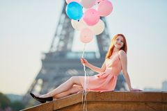 Girl with bunch of balloons in front of the Eiffel tower in Paris Stock Photo