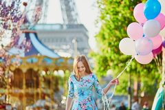 Girl with bunch of balloons in front of the Eiffel tower in Paris Royalty Free Stock Image