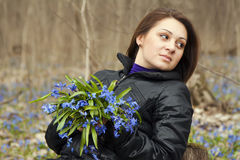 A girl with bunch of bluebells. In spring forest Royalty Free Stock Photo
