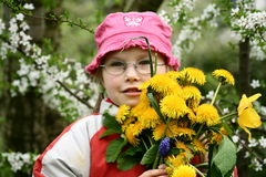 Girl with a bunch of flowers. A girl with glasses holding a bunch of dandelions and another spring flowers Royalty Free Stock Photo