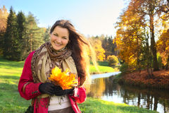 Girl with Bunch of Leaves. Beautiful girl with bunch of maple leaves in autumn park Royalty Free Stock Photo